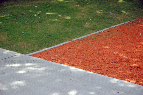 intersection of lawn, red gravel and pavement